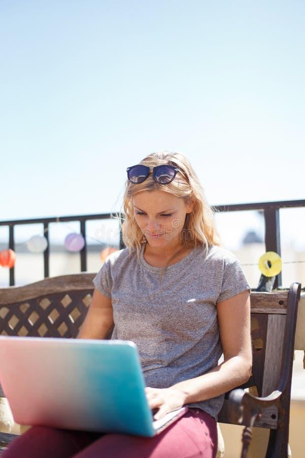 Mulher loura nova que datilografa no portátil que senta-se no banco foto de stock