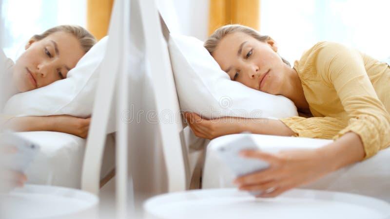 Mulher loura nova que datilografa no telefone ao encontrar-se em uma cama fotografia de stock
