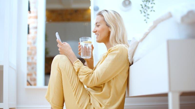 Mulher loura nova que datilografa no telefone ao sentar-se em um assoalho foto de stock royalty free