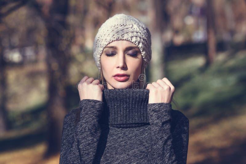Mulher loura nova que está em um parque com cores do outono fotografia de stock