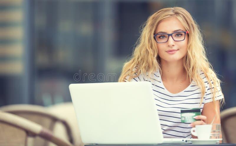 Mulher loura nova que guarda o cartão de crédito e que usa o computeron do portátil o terraço do caf fotografia de stock
