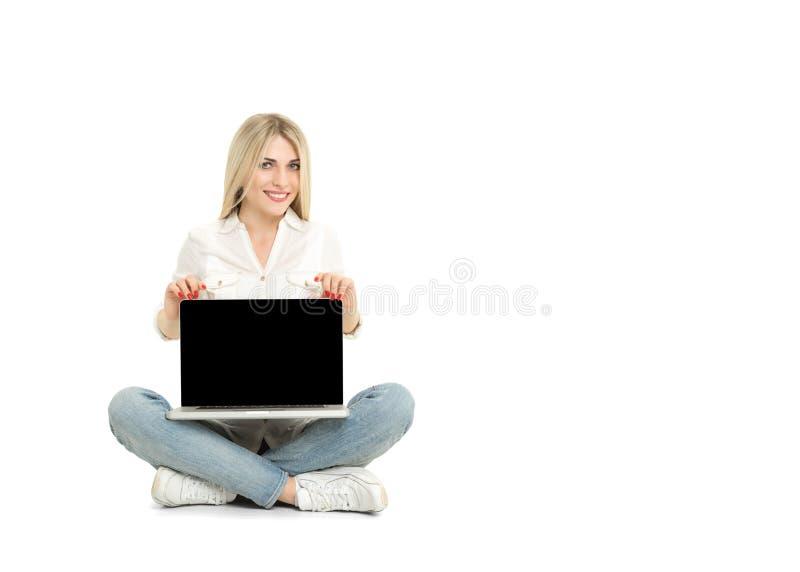 Mulher loura nova que mostra a tela de laptop vazia imagens de stock royalty free