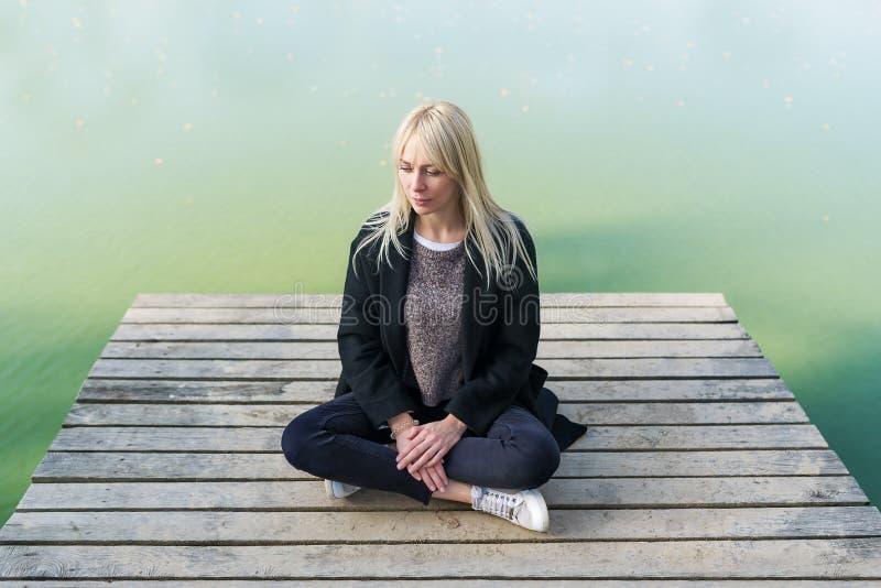 Mulher loura nova que senta-se na pose dos lotos no cais no outono no fundo do lago imagens de stock royalty free
