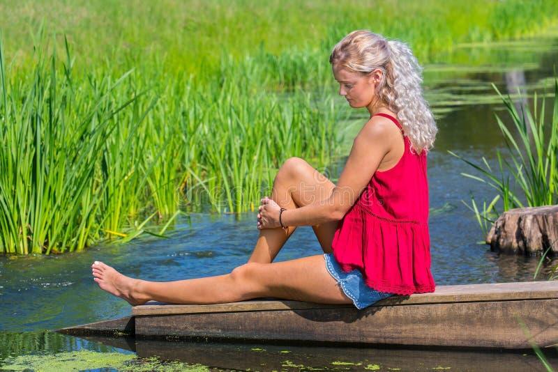 Mulher loura nova que sonha acordado na água na natureza foto de stock