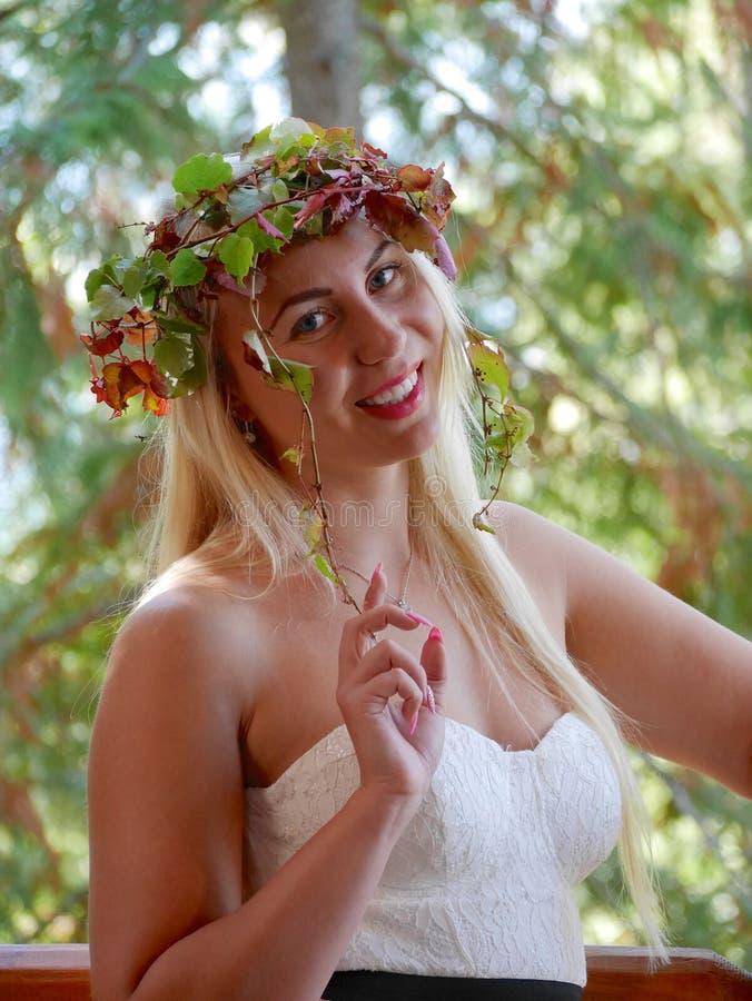 Mulher loura nova que sorri com Autumn Leaves Crown na cabeça imagem de stock