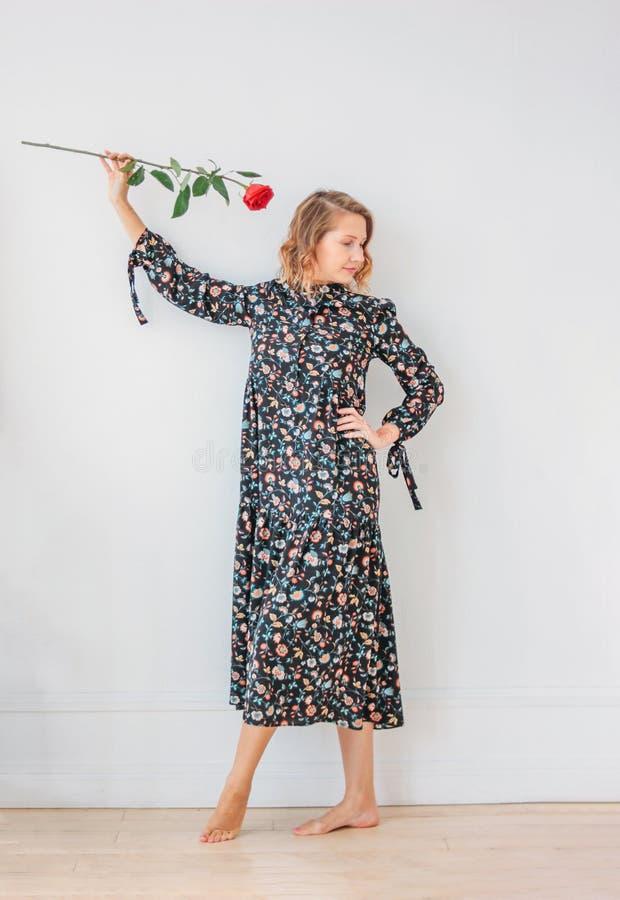 Mulher loura nova romântica bonita no vestido com a rosa vermelha no fundo branco do walll, retrato completo do comprimento imagem de stock royalty free
