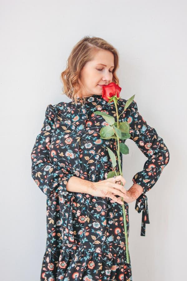 Mulher loura nova romântica bonita no vestido com a rosa vermelha no fundo branco do walll, retrato completo do comprimento fotografia de stock royalty free