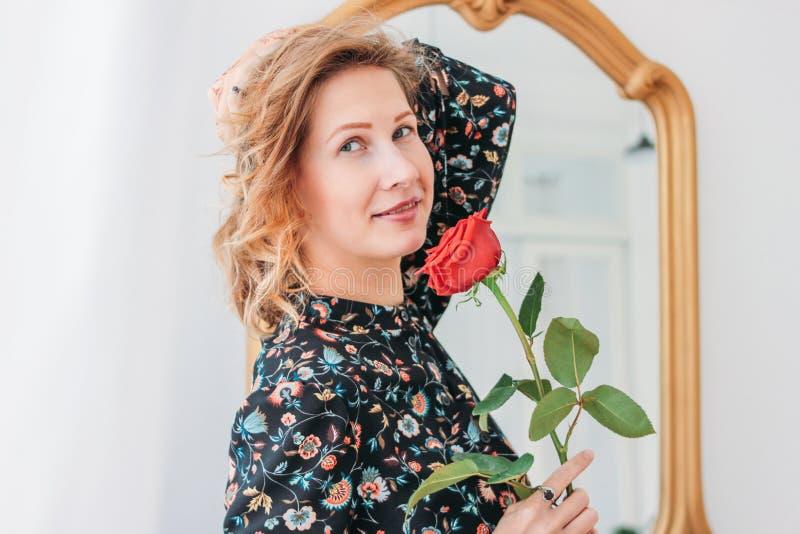 Mulher loura nova romântica bonita no vestido com a rosa vermelha perto do espelho foto de stock royalty free