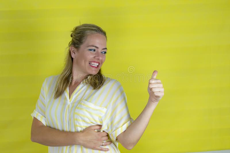 Mulher loura nova sobre o fundo isolado que sorri com a cara feliz que olha e que aponta ao lado com polegar acima fotos de stock