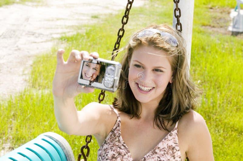 A mulher loura nova toma um retrato de auto com uma câmera fotografia de stock royalty free