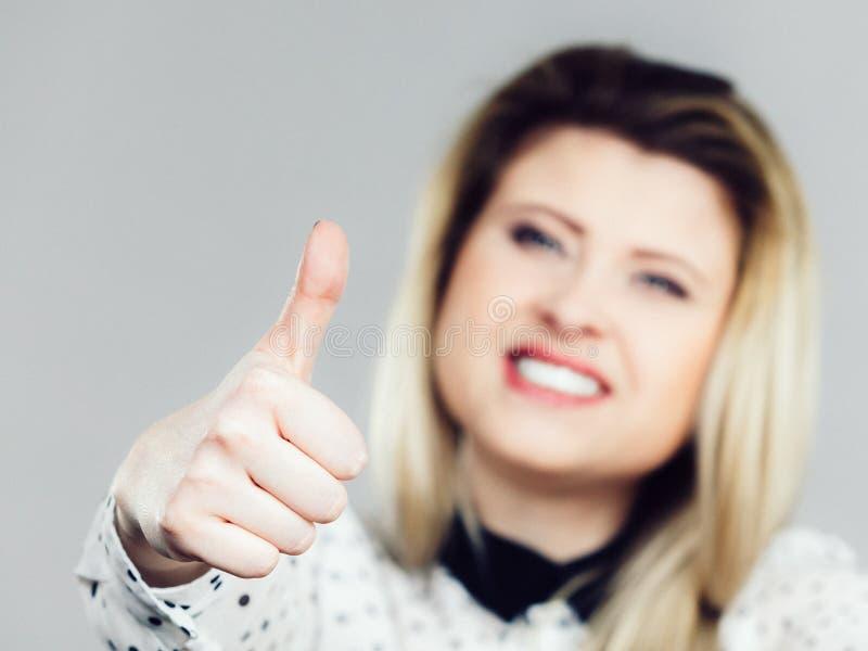 Mulher loura positiva feliz que mostra o polegar acima do gesto imagens de stock