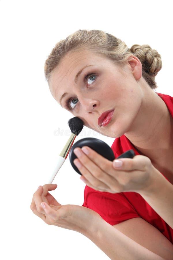 Mulher loura que aplica o ruge foto de stock