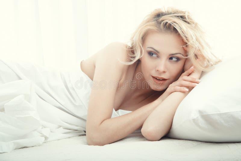 Mulher loura que coloca na cama no quarto fotos de stock