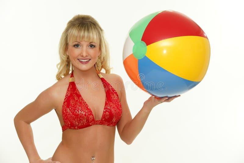 Mulher loura que desgasta a esfera de praia vermelha da terra arrendada do biquini imagem de stock