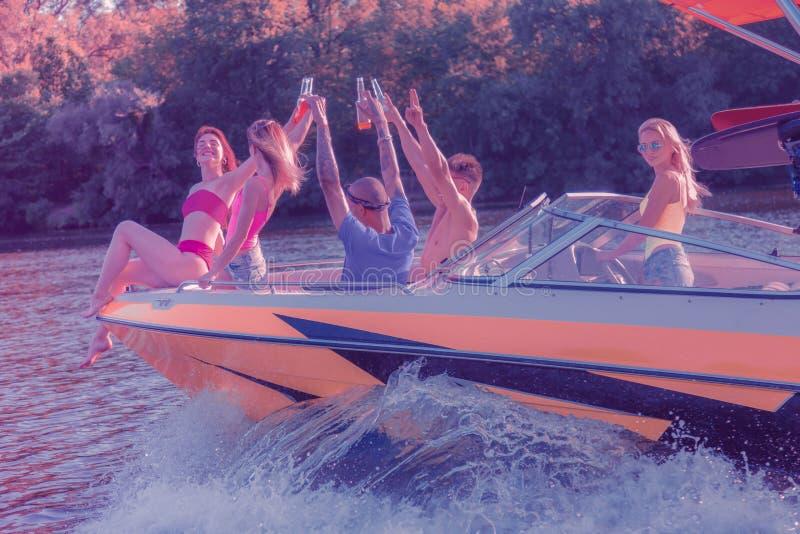 Mulher loura que dirige um barco com seus amigos foto de stock