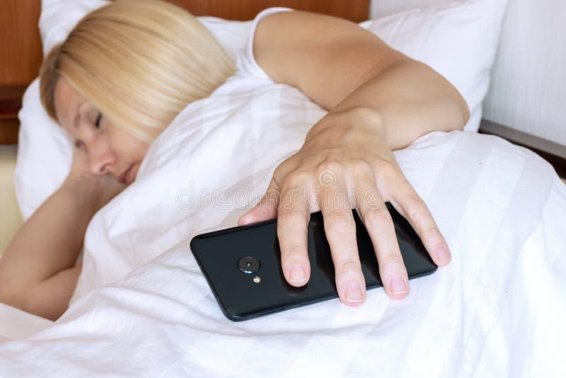 Mulher loura que dorme na cama com um smartphone à disposição imagem de stock