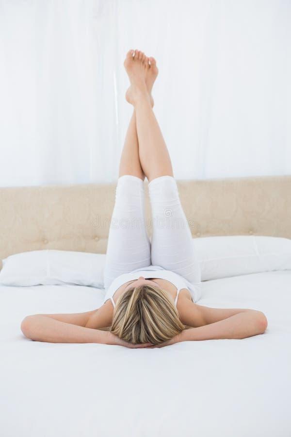 Mulher loura que encontra-se com pés acima na cama foto de stock royalty free