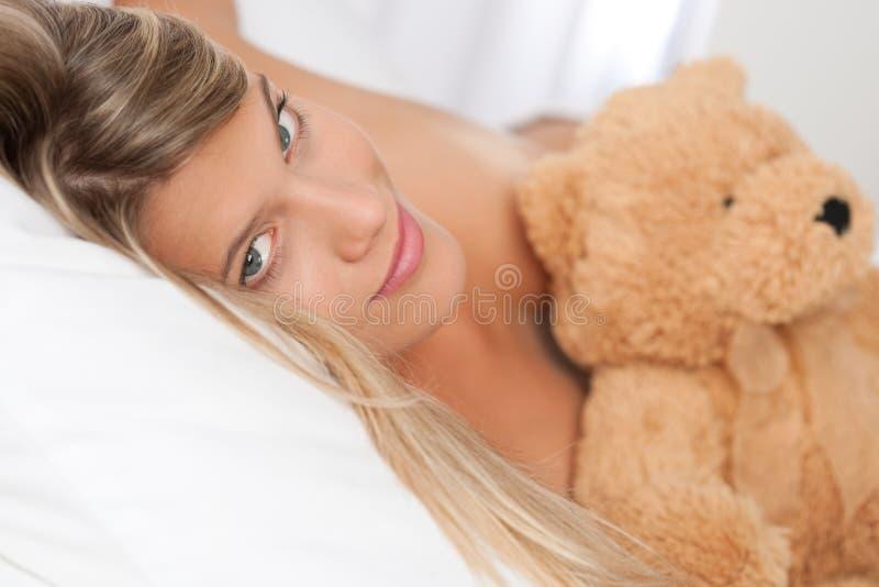 Mulher loura que encontra-se na cama com urso de peluche imagens de stock royalty free
