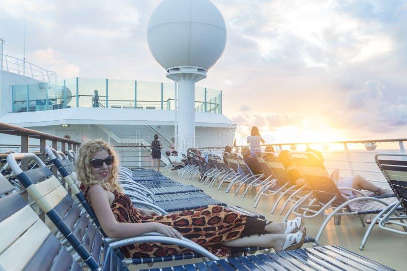 Mulher loura que encontra-se no sunbed no navio de cruzeiros durante o por do sol foto de stock