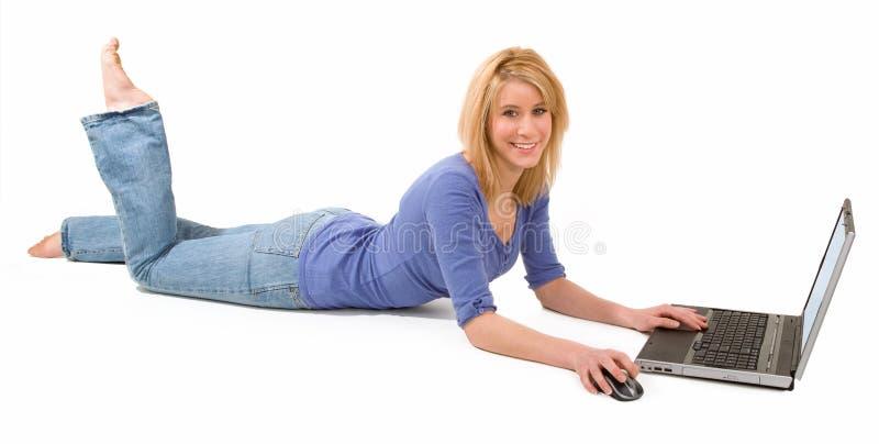 Mulher loura que encontra-se para baixo e que usa o portátil fotografia de stock