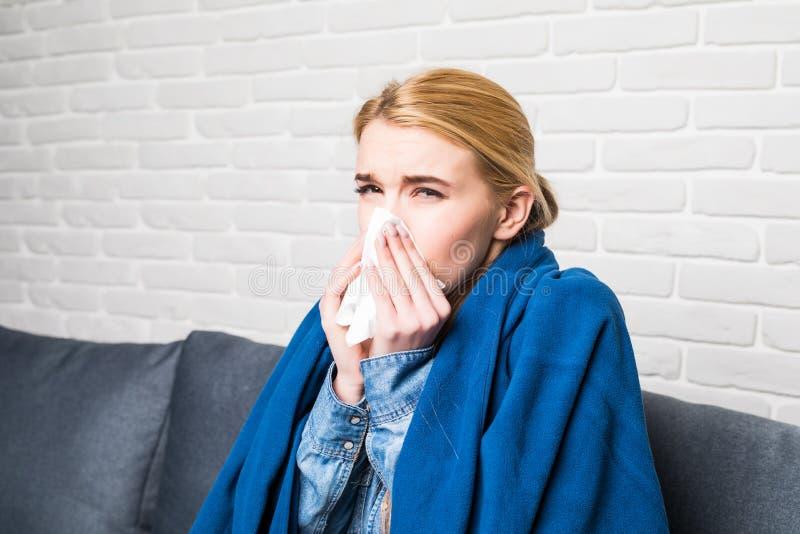 Mulher loura que espirra em um tecido no sofá na sala de visitas imagens de stock