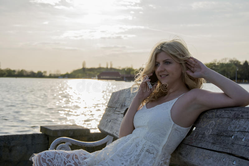 Mulher loura que fala no telefone pelo lago imagens de stock royalty free