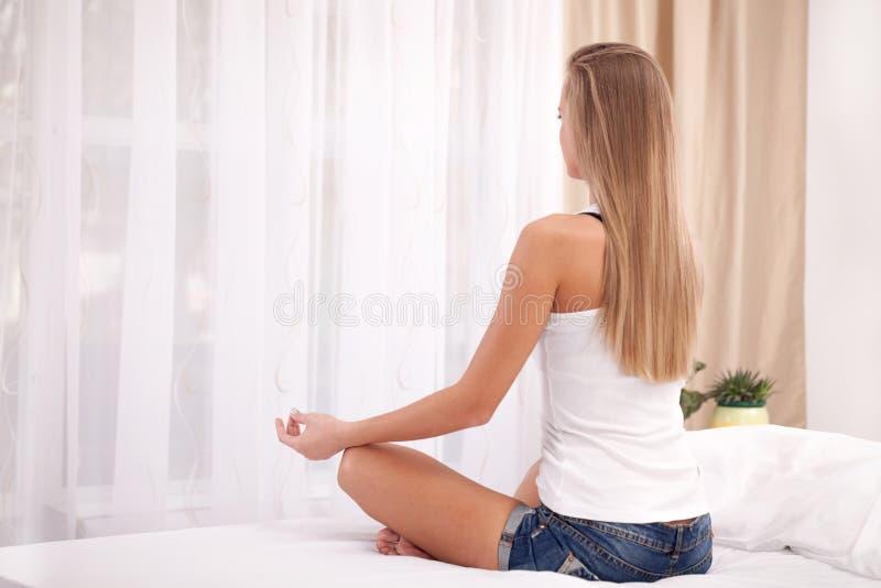 Mulher loura que faz a ioga na cama em casa no quarto foto de stock