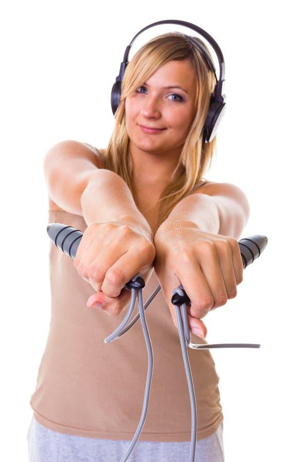 Mulher loura que guarda fones de ouvido vestindo da corda de salto fotografia de stock