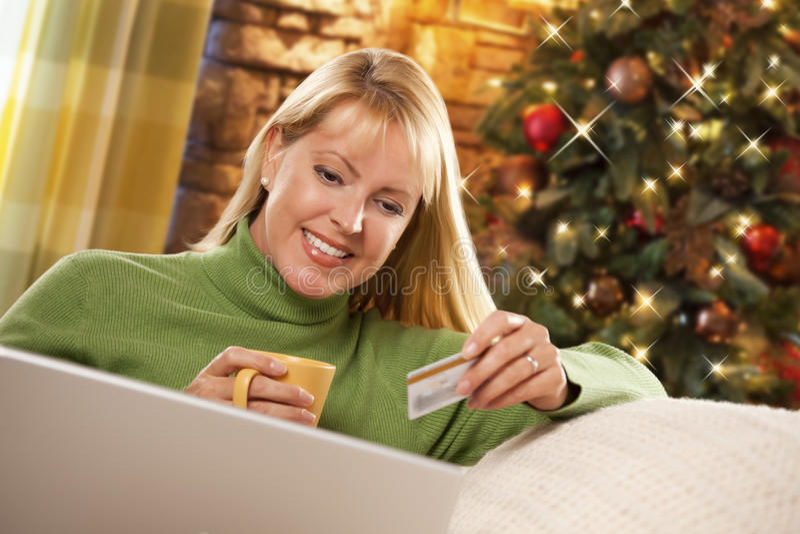 Mulher loura que guarda o cartão de crédito usando o portátil perto da árvore de Natal imagem de stock royalty free