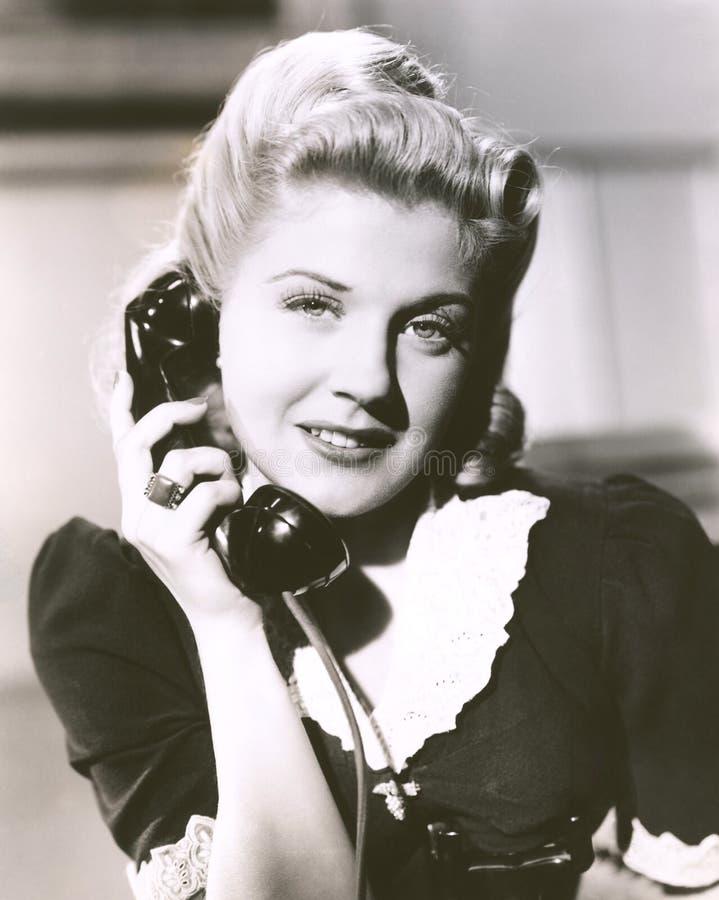 Mulher loura que guarda o receptor de telefone foto de stock