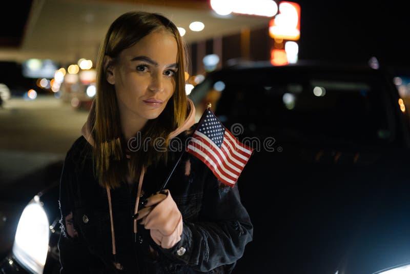Mulher loura que guarda o retrato da bandeira americana na noite na frente do luxo e da forma automobilísticos caros imagens de stock