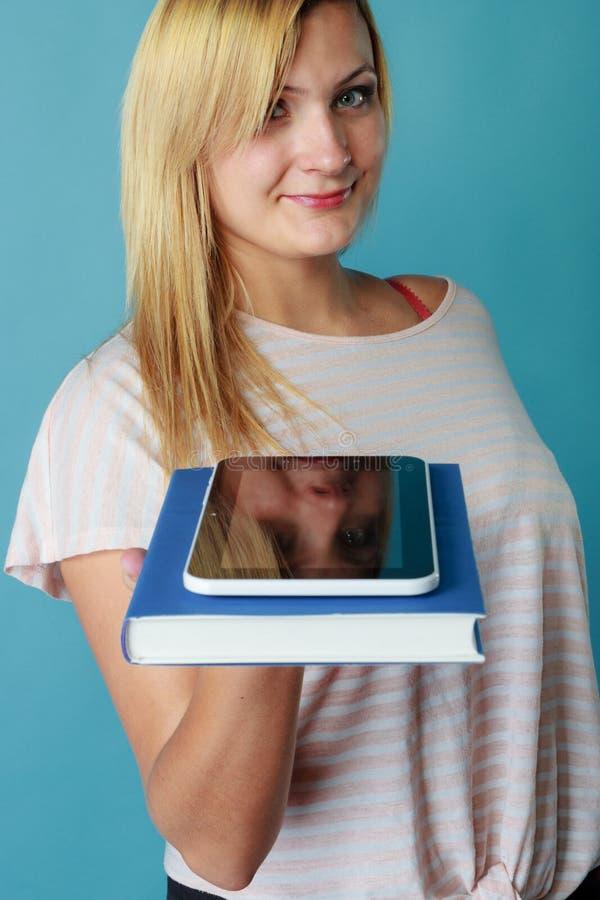 Mulher loura que guarda a pilha do livro e da tabuleta fotografia de stock