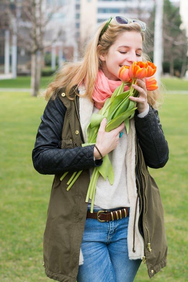 Mulher loura que guarda tulipas alaranjadas imagens de stock royalty free