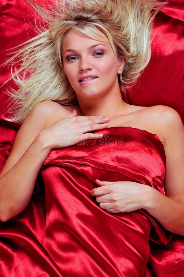 Mulher loura que morde seu bordo na cama foto de stock royalty free