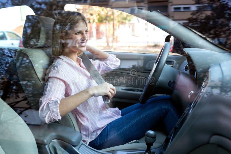 Mulher loura que põe o seatbelt antes de conduzir imagens de stock