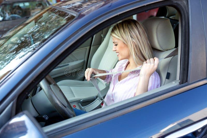 Mulher loura que põe o seatbelt antes de conduzir imagem de stock royalty free