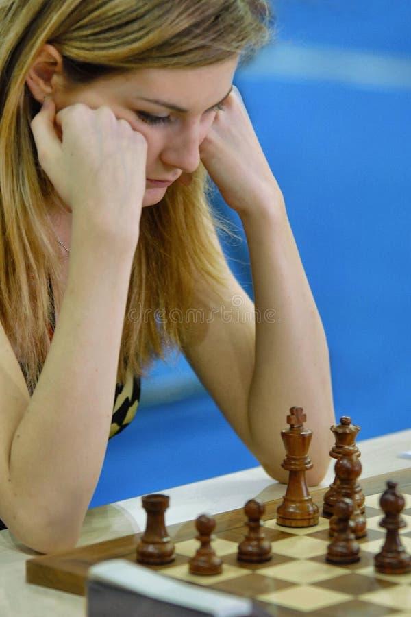Mulher loura que pensa durante o jogo de xadrez fotografia de stock royalty free