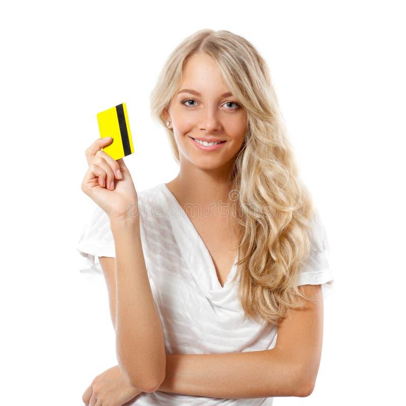Mulher loura que prende o cartão de crédito amarelo fotografia de stock royalty free