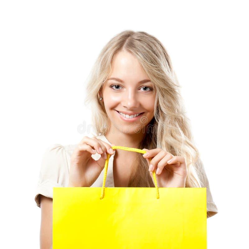 Mulher loura que prende o saco de compra amarelo fotos de stock royalty free