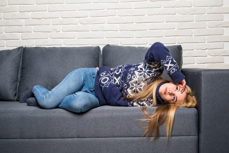 Mulher loura que relaxa em seu sofá branco em casa imagem de stock