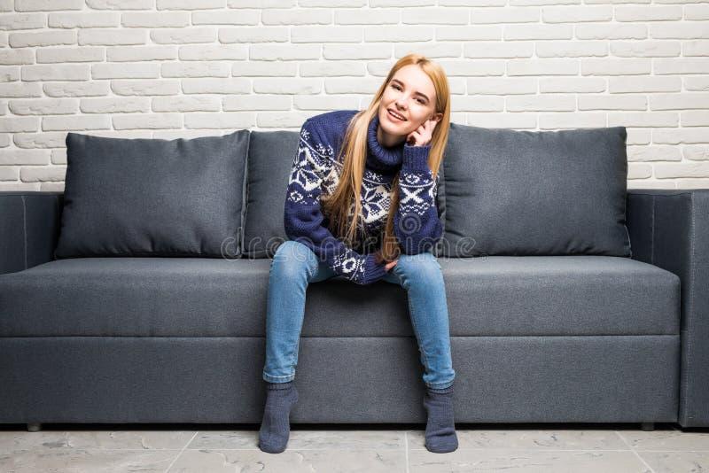 Mulher loura que senta-se em seu sofá branco em casa fotos de stock