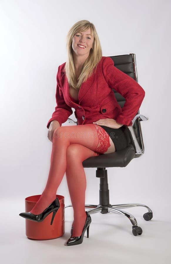 Mulher loura que senta-se em uma cadeira preta executiva fotografia de stock
