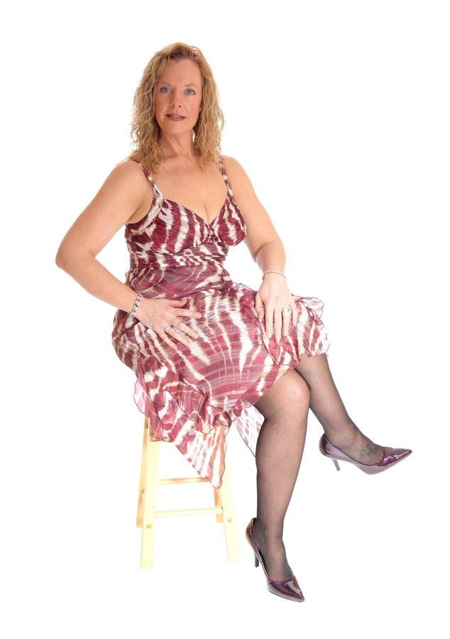 Mulher loura que senta-se na cadeira fotos de stock