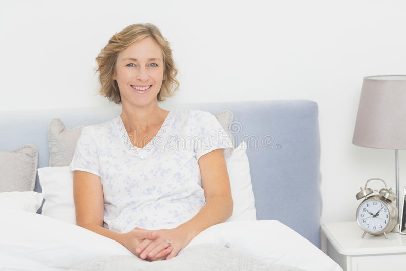 Mulher loura que senta-se na cama que sorri na câmera fotografia de stock