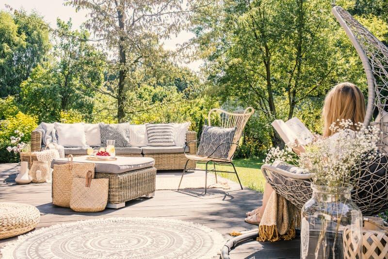 Mulher loura que senta-se no terraço de uma leitura da retirada de verão fotografia de stock