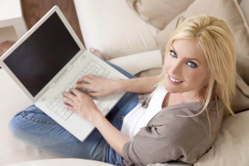 Mulher loura que usa o computador portátil em casa no sofá