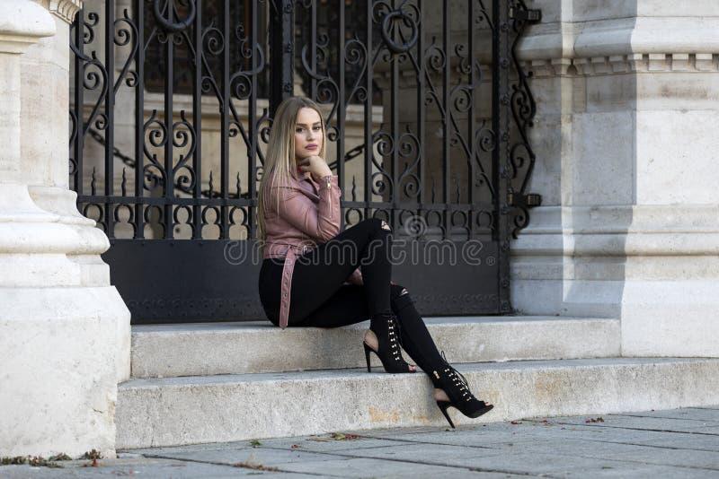 Mulher loura que veste calças de brim e o casaco de cabedal pretos foto de stock royalty free