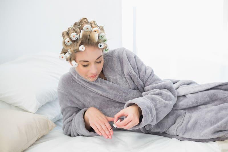 Mulher loura relaxado concentrada nos encrespadores de cabelo que aplicam o verniz para as unhas imagem de stock royalty free