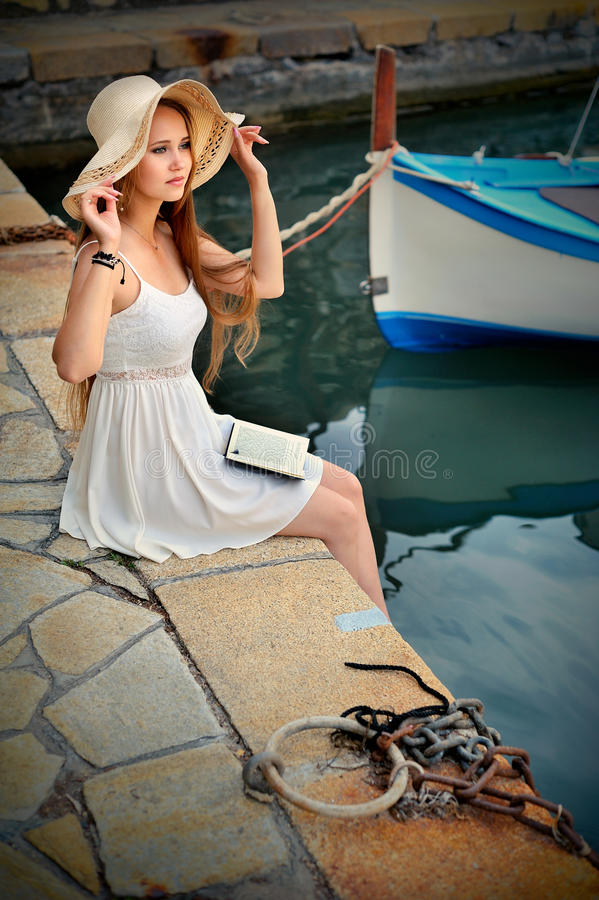 Mulher loura romântica com chapéu e cabelo longo Barco no fundo do mar imagens de stock