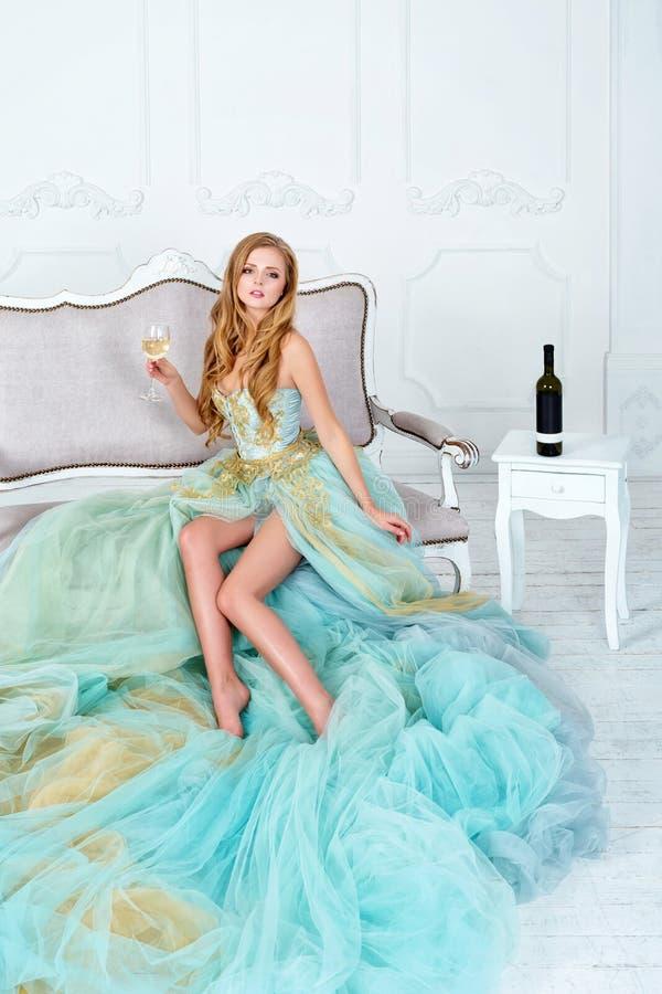 Mulher loura sensual bonita no vestido longo lindo que guarda o vidro do vinho branco e da garrafa Comemoração da moça foto de stock royalty free